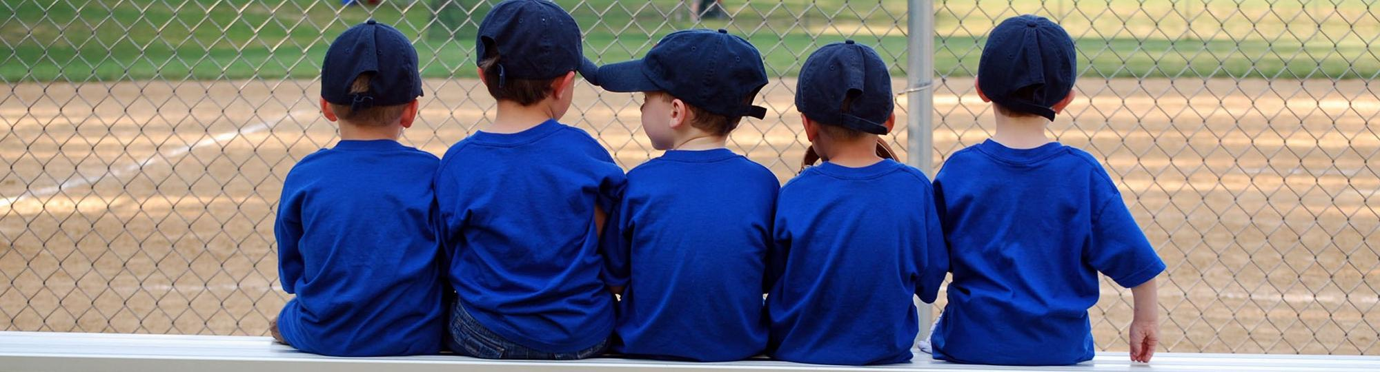 Rear view of a row of kids in blue baseball caps and T-shirts sitting on a bench at a ballfield