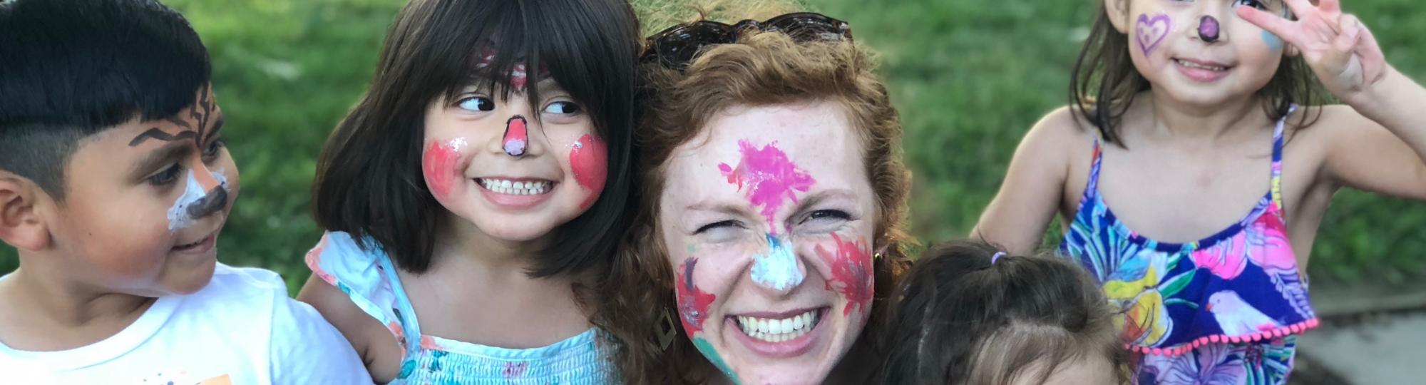 Smiling children and young woman wearing colorful face paint