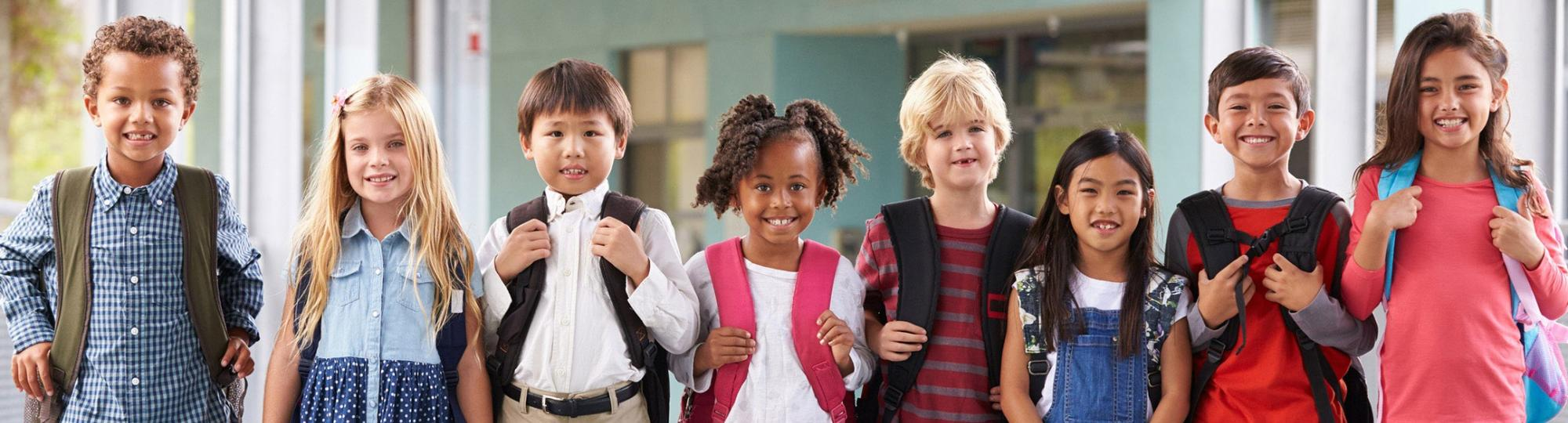 Smiling, ethnically diverse schoolchildren in colorful clothes and backpacks are lined up side by side