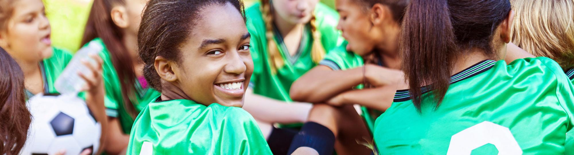 Girls in bright green soccer jerseys, one turning to the camera and smiling