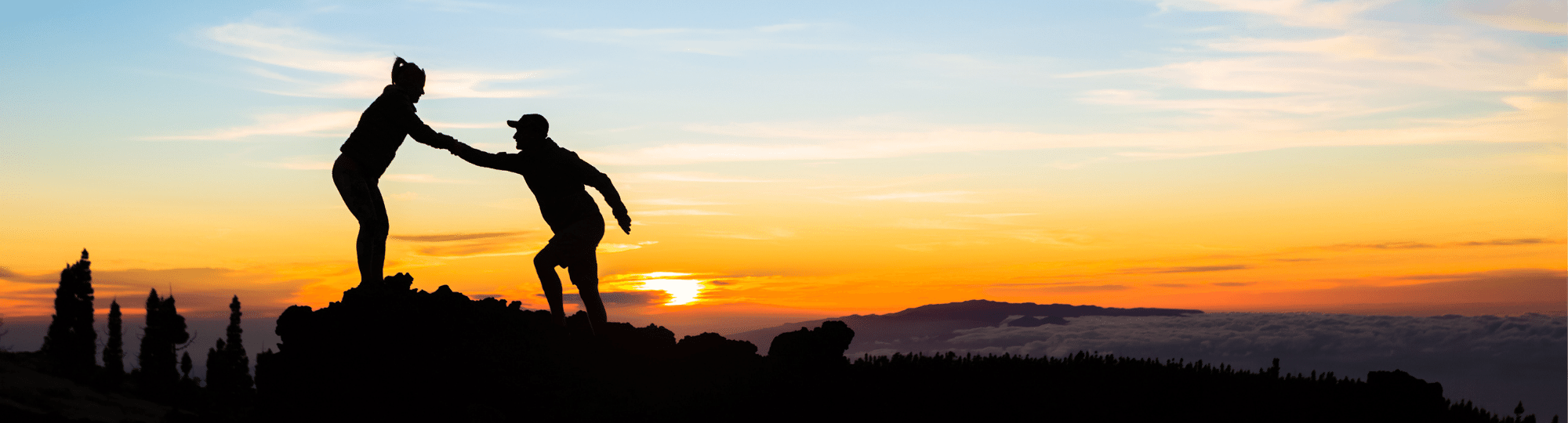 Silhouette of one person helping another to the top of a hill, with sunset behind them