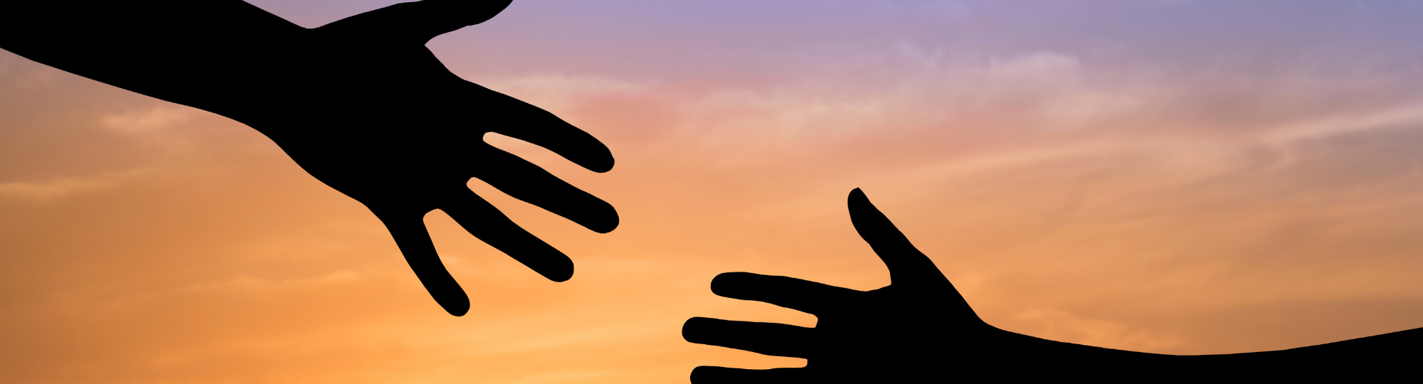 A helping hand reaches for another hand, silhouetted against a colorful sunrise