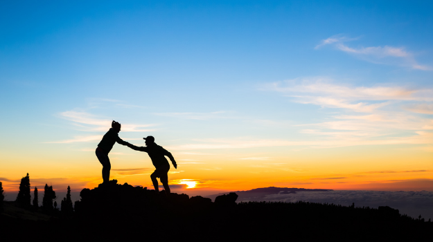 Silhouette of one person pulling another up to the top of a hill with sunset behind them